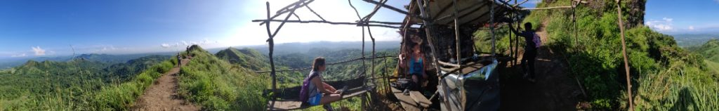 Hikers resting in a shack, drinking water, mountain views