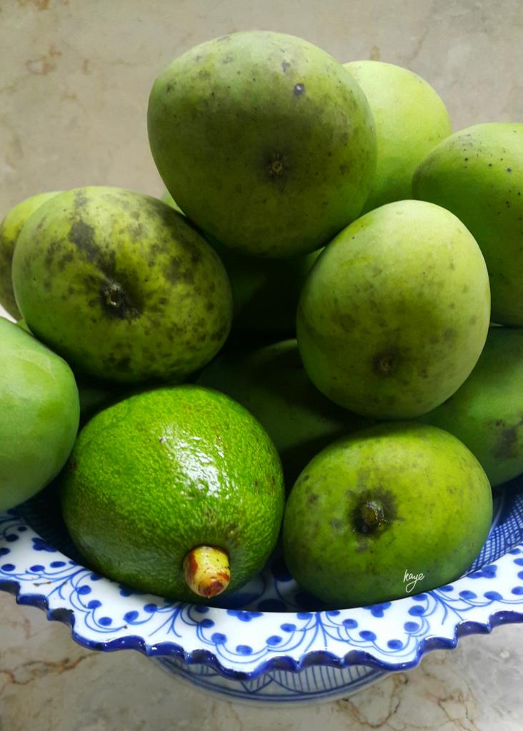 Green mangoes and an avocado