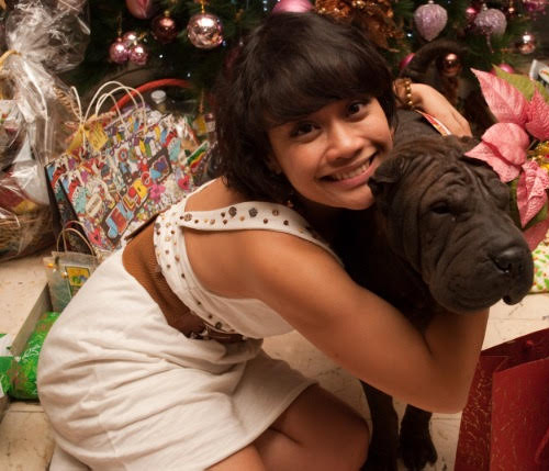 girl hugging black dog, holiday season